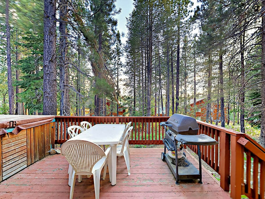 On the back deck, you'll find a gas grill and stairs down to the pretty backyard teeming with pines.