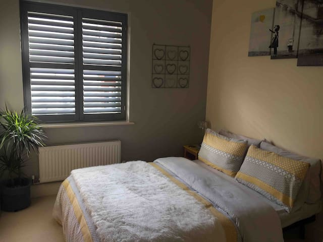 Cosy Bedroom with quality Handcrafted Shutters, Double Bed, Funky Yellow Chair inspired by Eames and Large Wardrobe with an abundance of Hanging Space, Wooden Hangers and Internal Shelving, Hairdryer, Personal White Robes and Chrome Fan