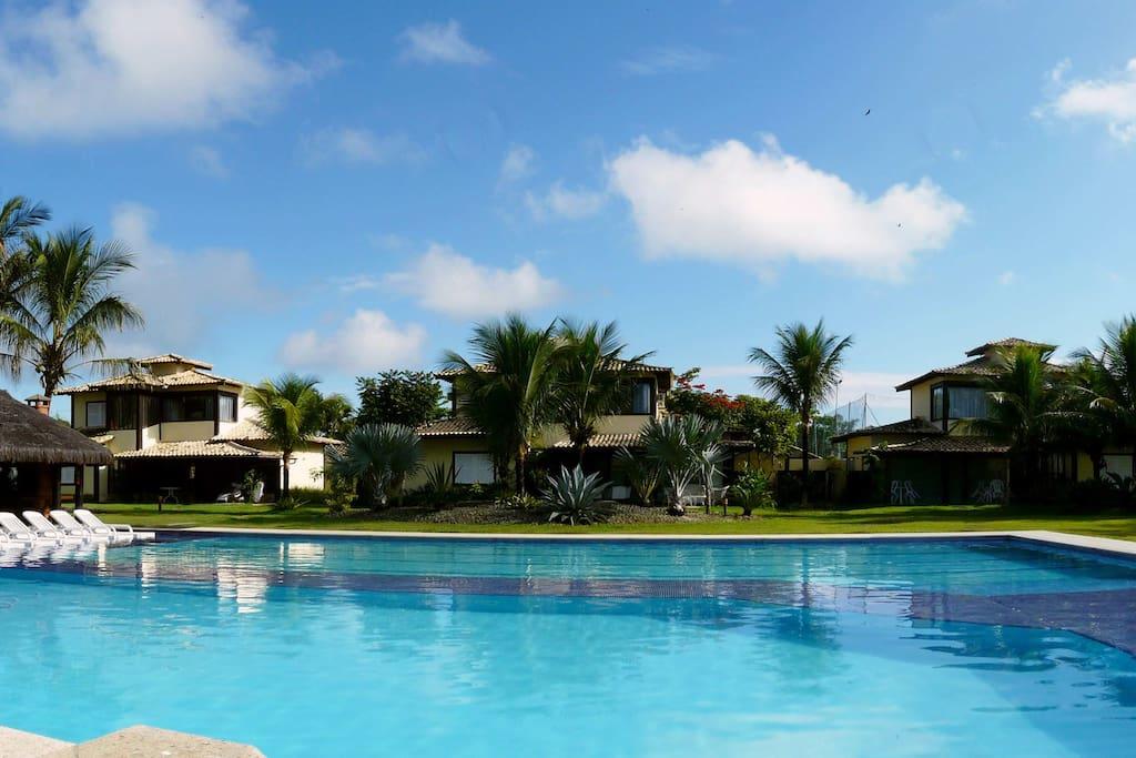 A maior piscina de Geribá, com bordas molhadas, cercada de um enorme jardim.