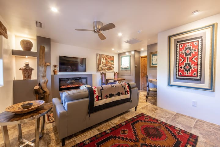 The living room has beautiful red rock views, an electric fireplace, large leather sofa, full kitchen and dining area for two.