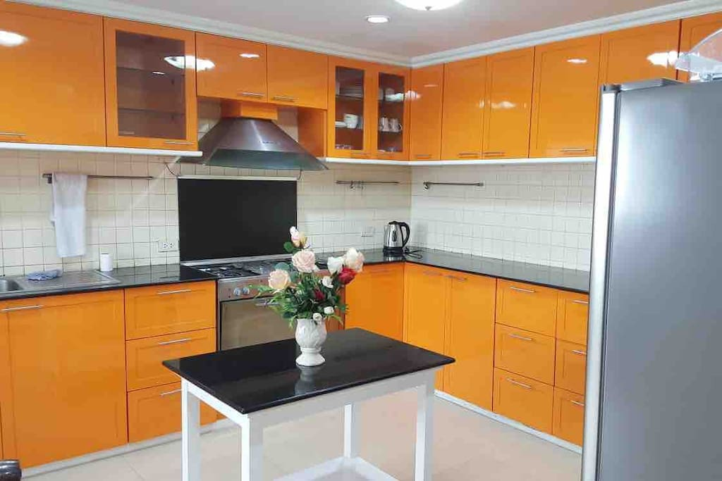 The fully equipped kitchen with refrigerator, microwave, stove, oven, kettle, utensils and pots and pans.