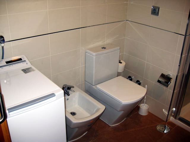 Bathroom with washing machine, bidet and toilet.