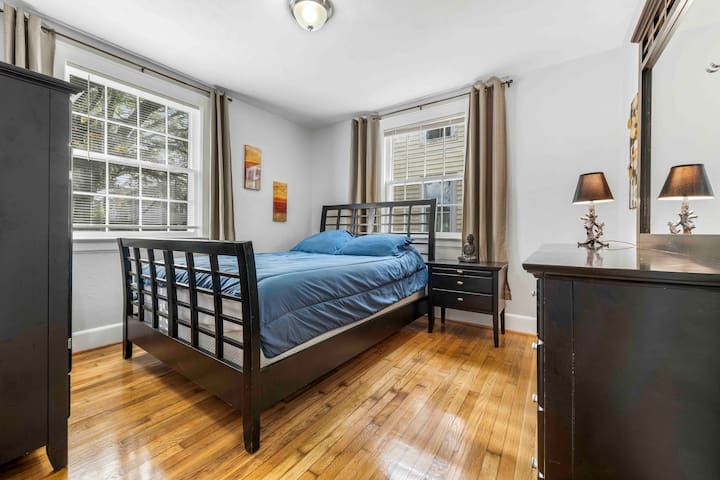 Timeless and comfy bedroom with solid wood features and room darkening blinds.