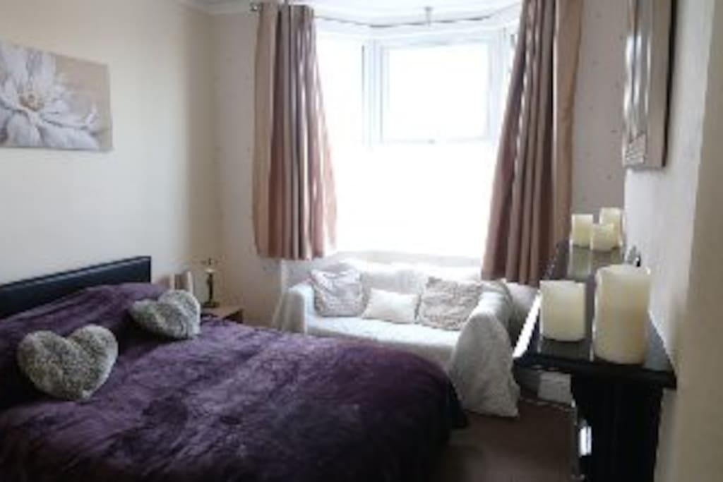 Bright fresh Spacious Bedroom with TV and Sofa.