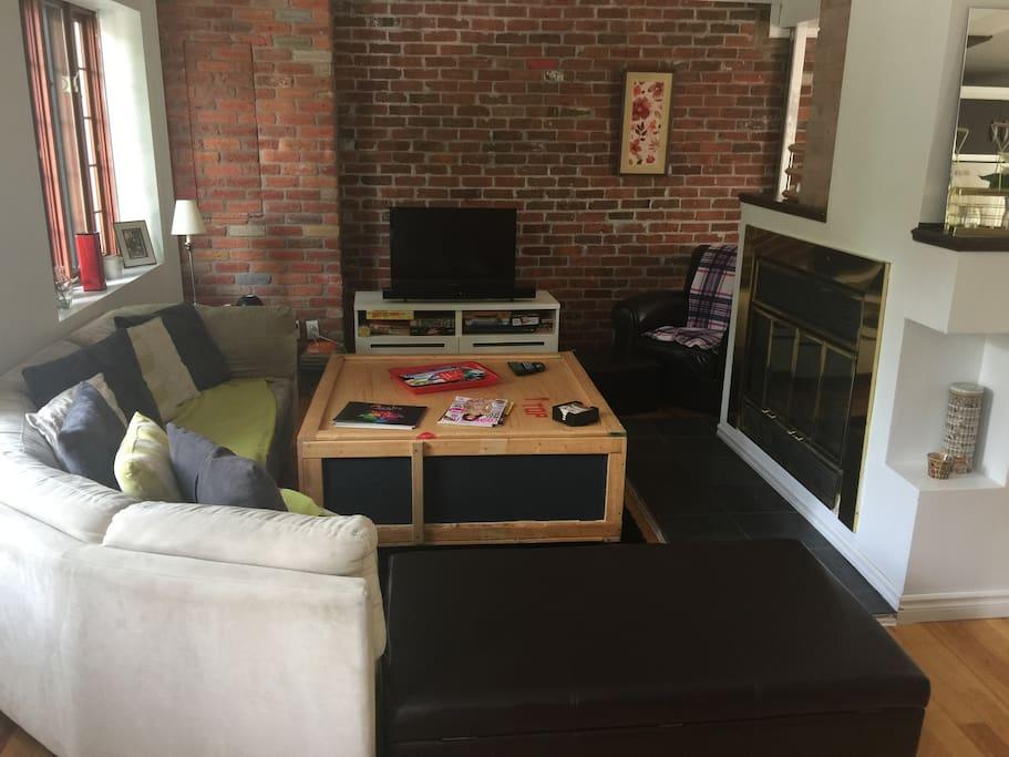 Living room with fonctionnal wood fire place / Salon ouvert avec cheminée au bois fonctionnelle.