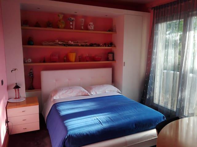 Stanza privata con letto matrimoniale, armadio, scrivania e terrazzino.
