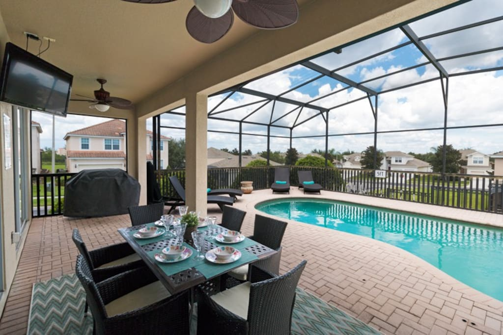 The lanai has outdoor seating for you to enjoy meals by the pool