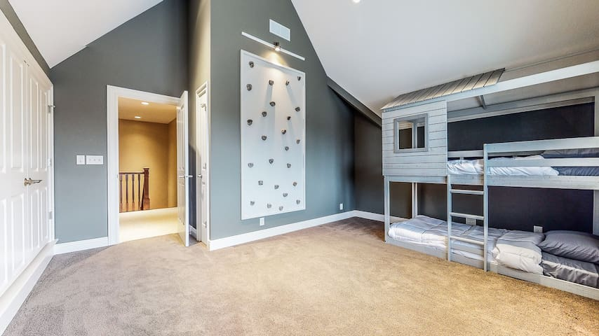 """This 3rd floor bedroom features bunk beds, rock climbing wall, vaulted ceilings, and 55"""" TV."""