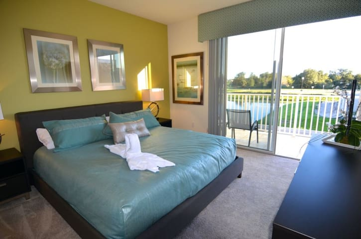 Stylish king master bedroom with en suite bathroom, balcony with water views, flat screen TV and walk-in wardrobe
