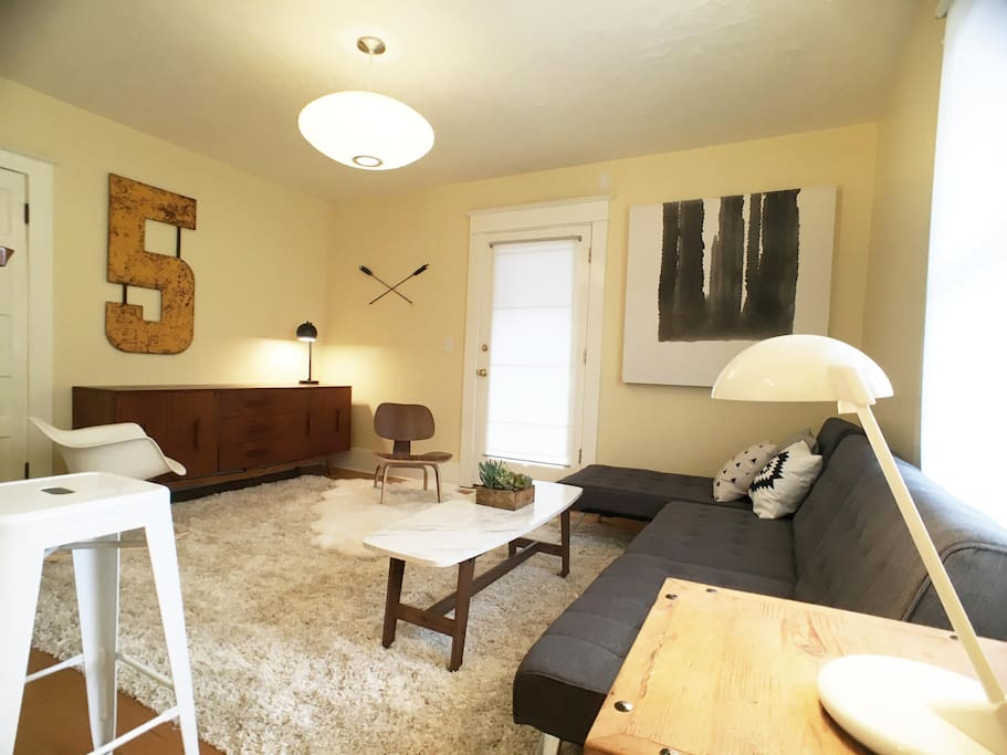 Living room has a nice mix of minimal mid century furnishings and original art, ample seating to kick back in