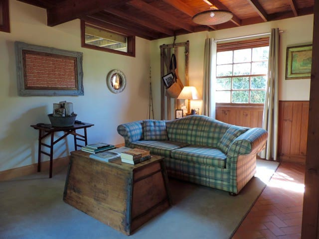 Cottage sitting room includes a comfortable sofa, artworks and numerous books and garden and food magazines.