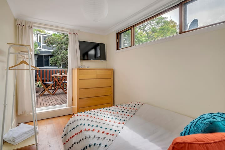 The second bedroom features a comfortable double bed, wall-mounted TV and access to a large outdoor patio.