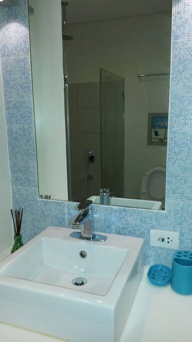 Bathroom: Glass covered shower room, sink and toilet with bidet.