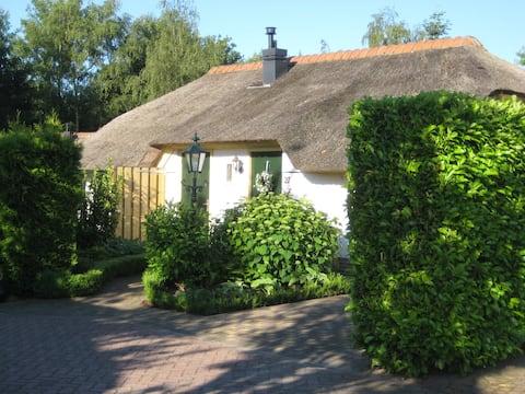 Knus wit huisje met rieten dak en royale tuin