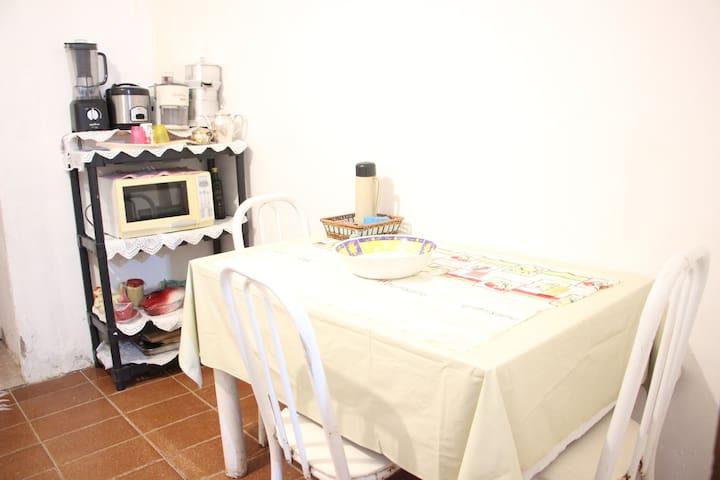 Microondas e mesa para refeições.