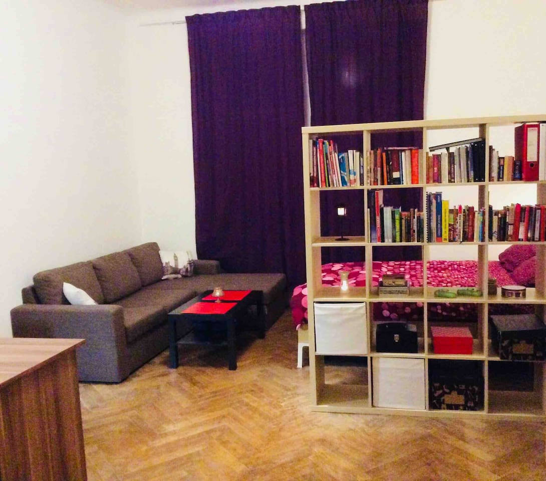 Second room is 25 sqm. Has one double full bed, big corner sofa with small conference table, solid desk, bookshelf and the wardrobe.