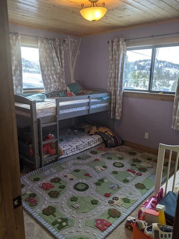 Cosy kids bunk room with twin bunk and additional crib.