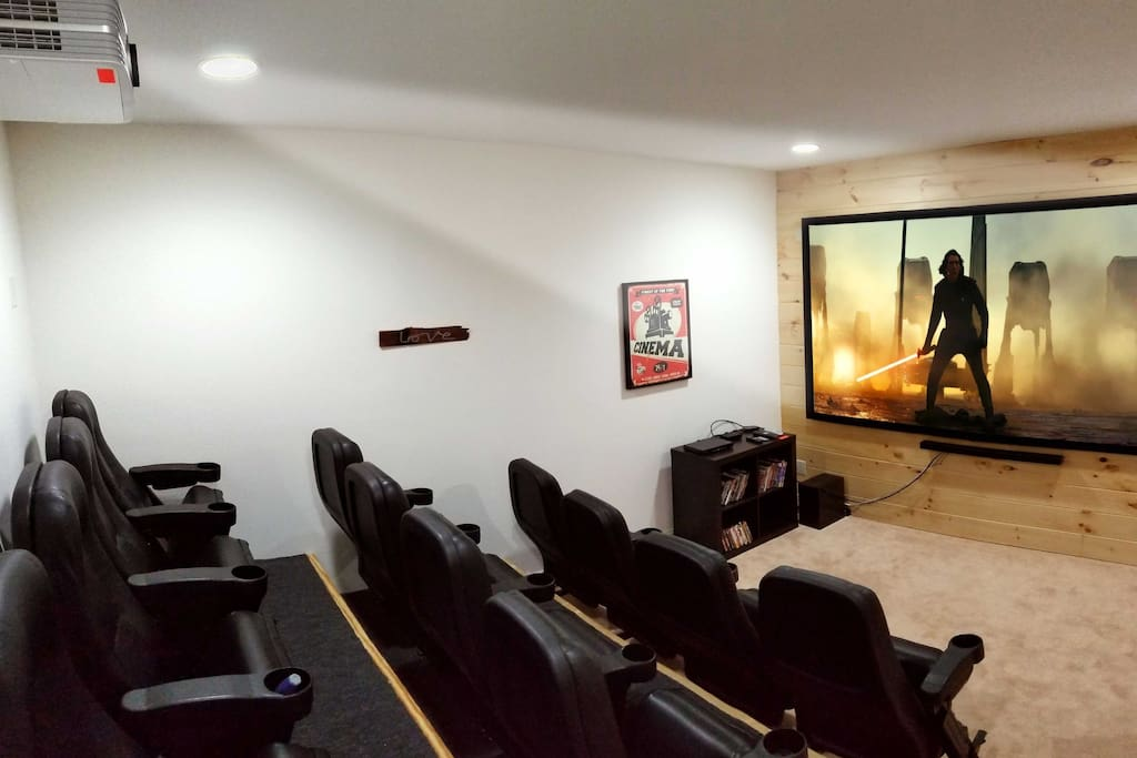 "The home movie theater boasts a 4K UHD video projector, 120"" screen & sound bar."