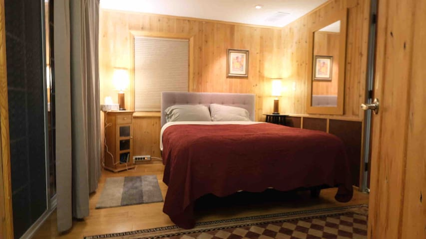 The bedroom. It features a queen bed with a new Posturepedic mattress.