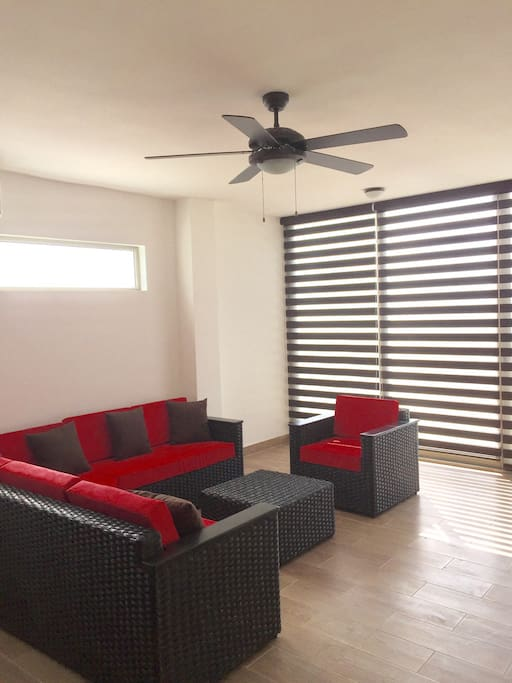 The living room with a wall to wall, floor to ceiling sliding doors and the view of the beach.