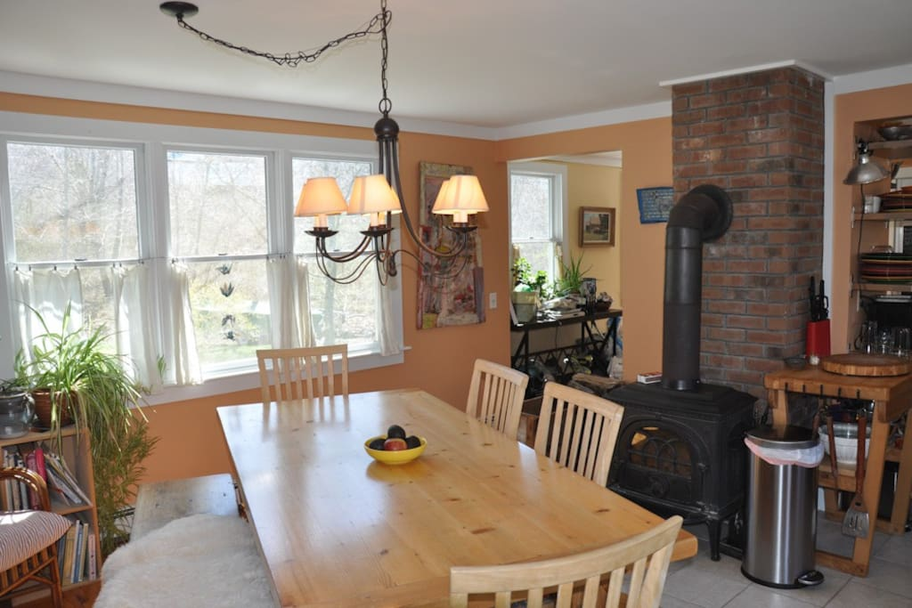 Dining table next to cozy wood stove.