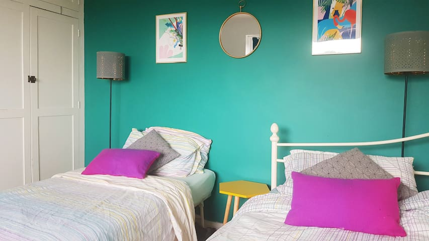 Colourful twin room in welcoming family home.