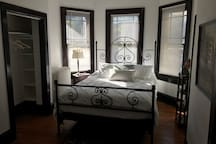 Hand-welded antique wrought iron queen sized bed with all new bedding and Sealy mattress.