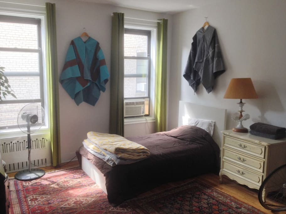Spacious bedroom with lots of natural light, storage space, and art-filled decor.