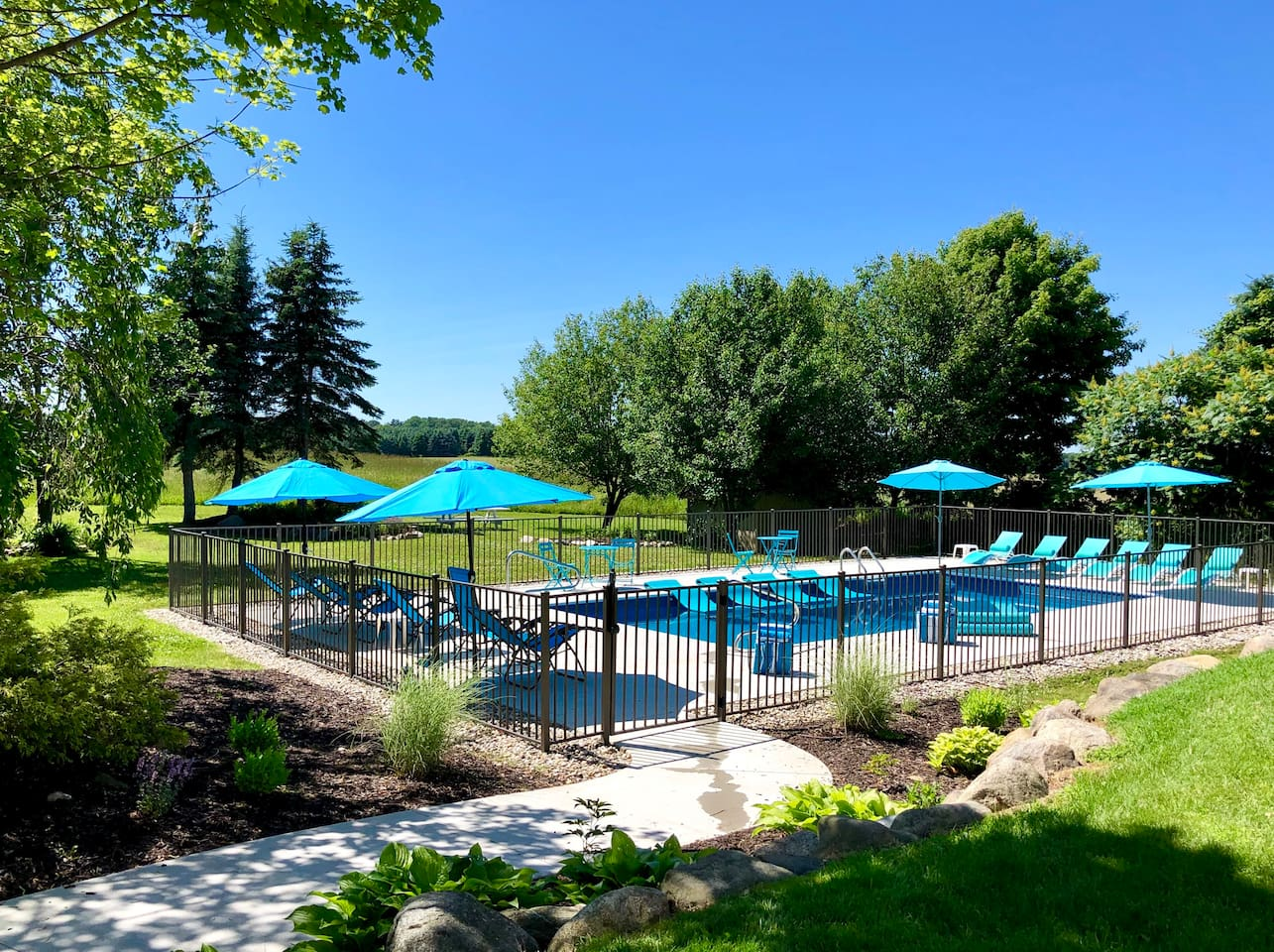 BACKYARD/POOL: Super-private 3 acres surrounded by farmland.  In-ground heated pool, deep&shallow ends, fence, self-locking security gate, umbrellas, rafts, pool loungers, deluxe noodles, pool/beach towels, white picnic table pictured in background.