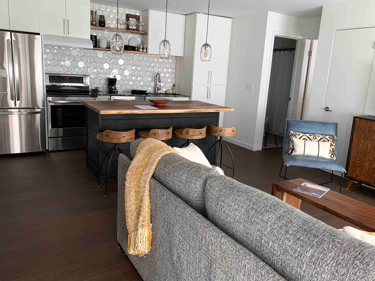 This open kitchen/living area has seating for 4 at the live edge wood island.  The couch pulls out to a queen size bed.
