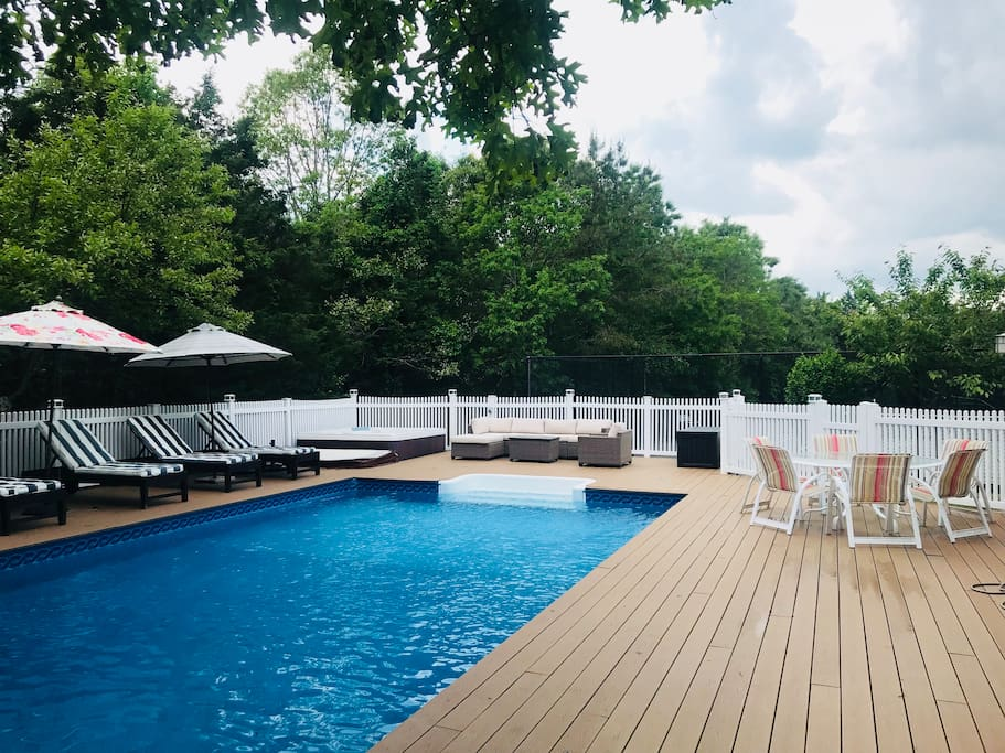 Heated pool with hot tub. Sun-filled deck with poolside loungers, umbrellas, BBQ grill, outdoor dining table and outdoor lounge area.