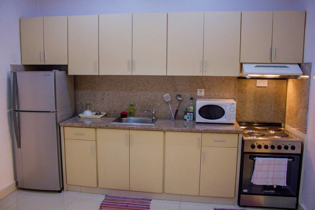 Kitchen that includes a microwave, refrigerator, and cooking necessities