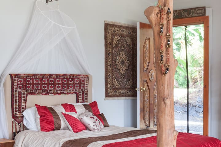 I have traveled the world and collected carpets from Arabia, India, South Africa and more. That is a camel saddle decoration above the bed. The carved wooden door is another rare find. At night the trade winds come through and lull me to sleep.