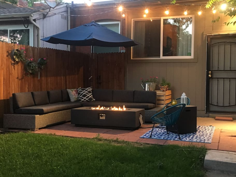 Quaint back yard with gas grill and fire pit.