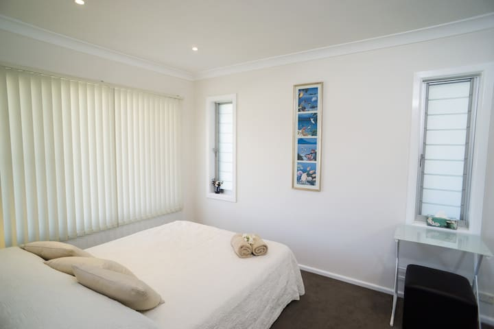 Comfortable bedroom with desk and large robe.
