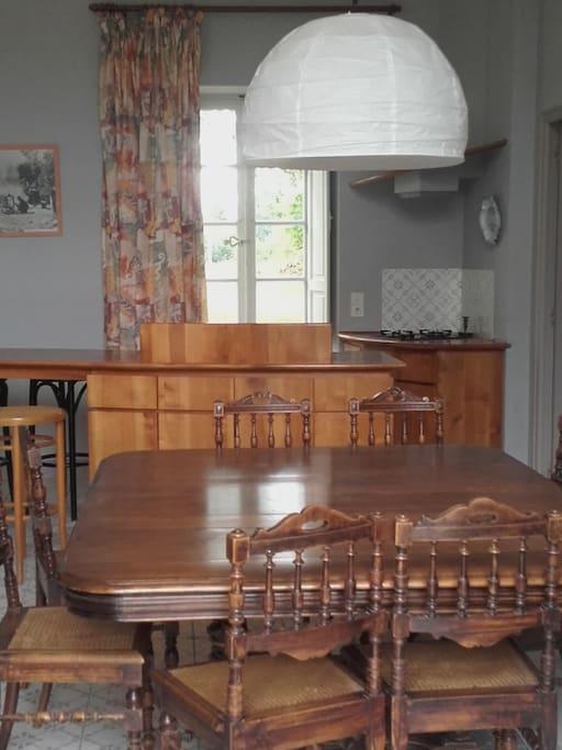 une table spacieuse très proche de la cuisine autant que de l'extérieur, pour des repas simples et faciles