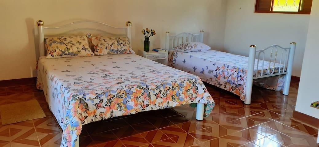 2 camas de casal 1 cama de solteiro Banheiro privativo Varanda  com cadeiras de descanso.