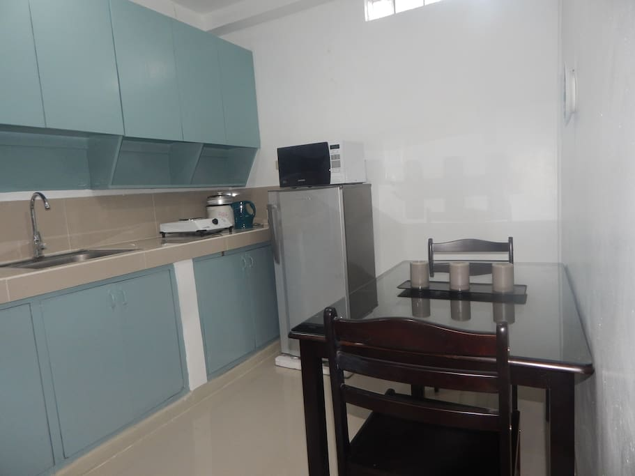 Kitchen with refrigerator, microwave, electric kettle, stove and rice cooker