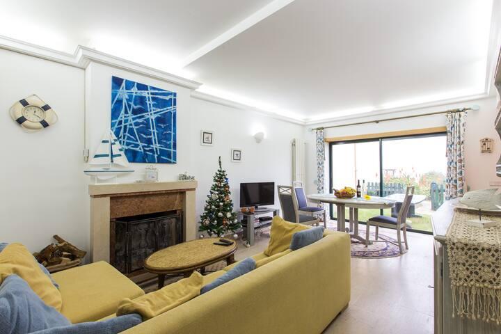 Sala de estar e de jantar, com lareira e acesso direto a jardim privado.