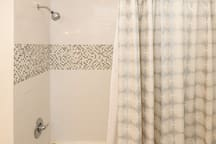 New shower tile, faucet, curtain.