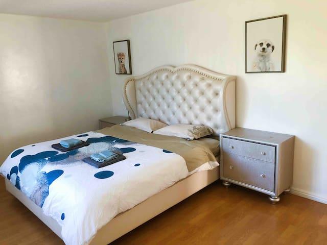 Room #1 with a king size bed and a wood regular sized baby crib 第1个房间,有国王尺寸大床和正常尺寸木质婴儿床,婴儿床可用于5岁以下小孩。