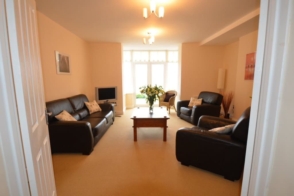 The Living Room is large with a log burning stove, french doors open out to the patio and garden furniture.