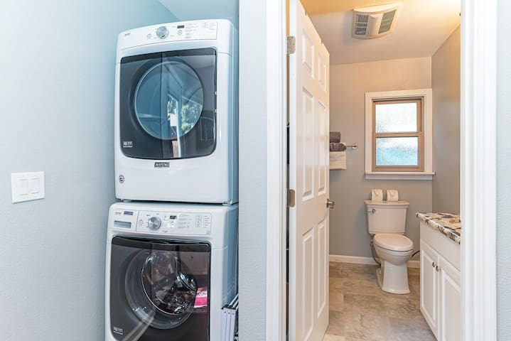 A full-size washer and dryer and laundry detergent as well as a drying rack.