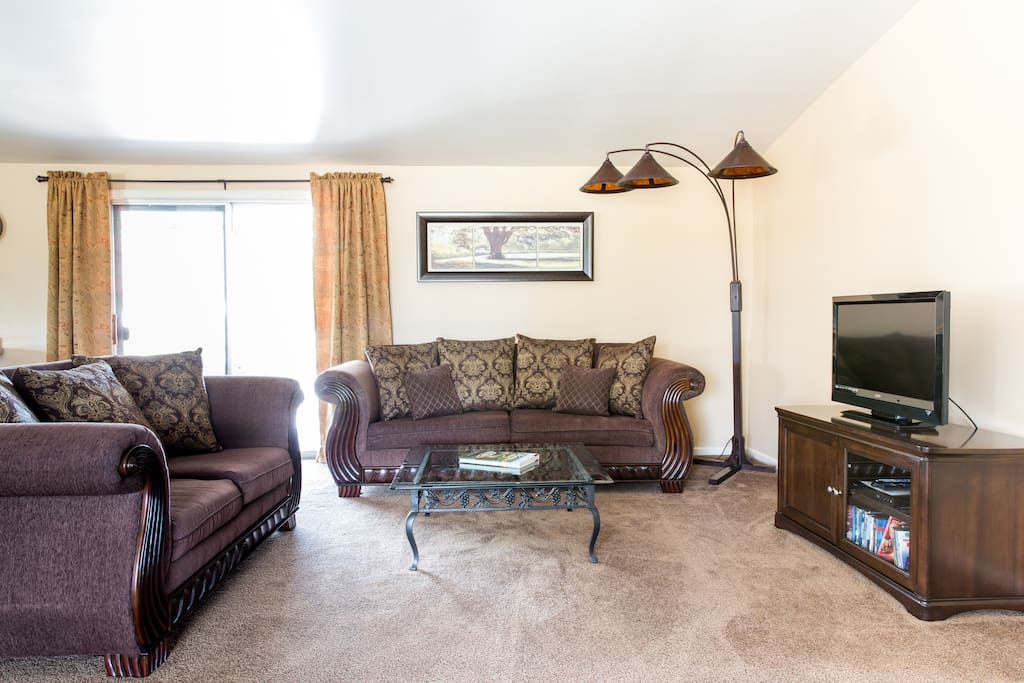 Large open concept great room with living room seating and a slider to the patio.