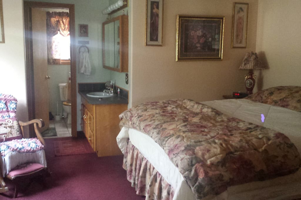King size bed with bathroom, shower attached.