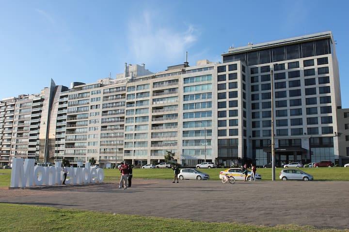 """El edificio es el que se observa arriba de la letra """"o"""" del cartel Montevideo y el que está más a la derecha es el hotel Hyatt. Al frente playa de Pocitos. Entre el hotel y el edificio se encuentra la cafetería Deli."""
