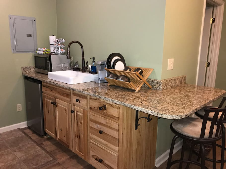 Granite countertop, farm sink, microwave, dishes and utensils, Keurig Coffee maker, with a wide variety of flavors to choose from. Snacks and water bottles also provided.