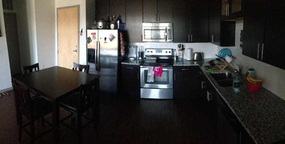 Stainless steel appliances, and wood cabinets + table.