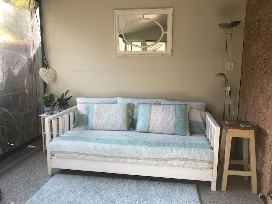 Daybed for 1 extra guest to sleep,  is an enclosed verandah with clear cafe blind viewing onto a garden