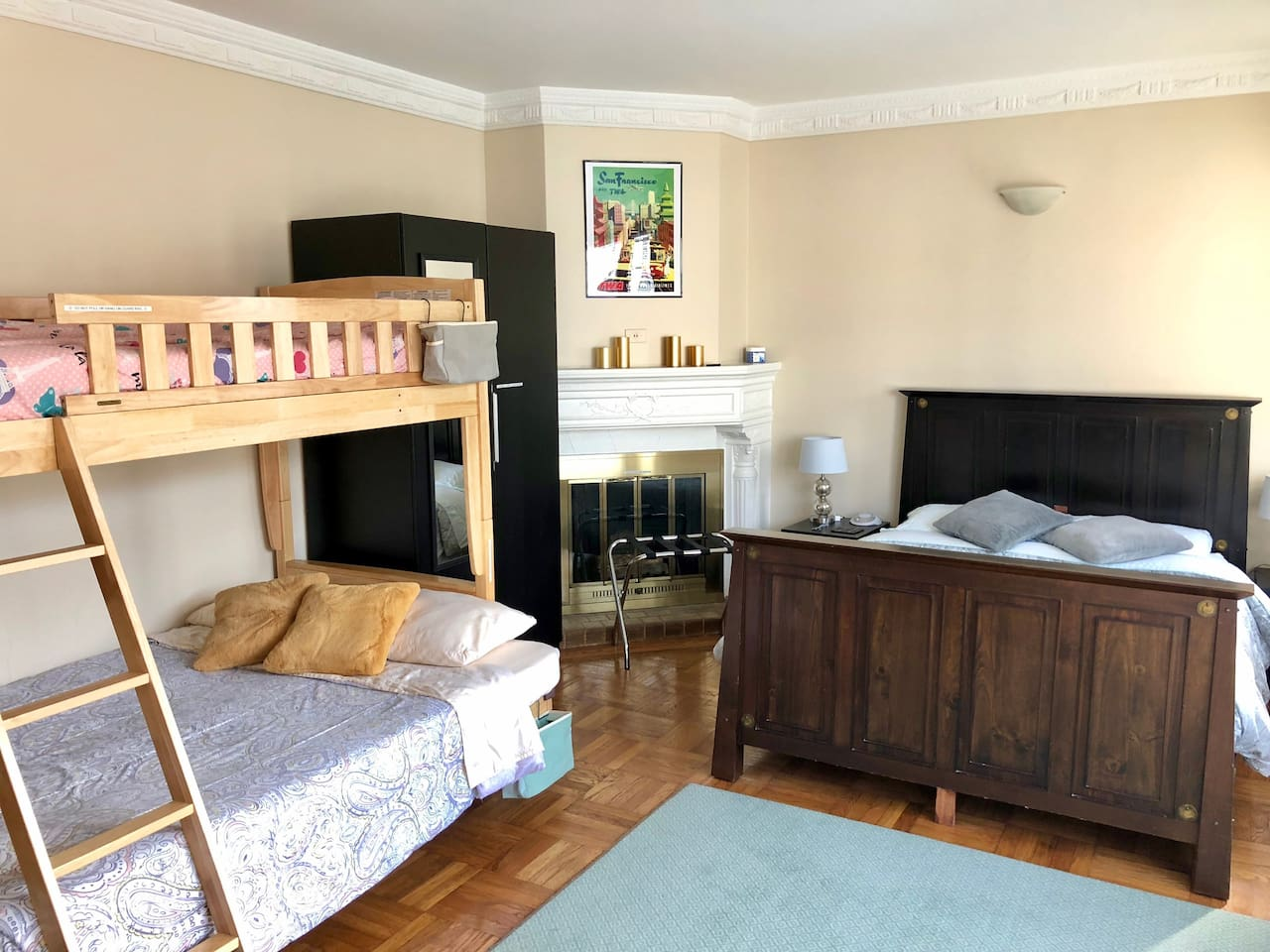 This room features a queen bed, bunk beds (full futon mattress on bottom and twin mattress on top), table and chairs, easy chair, wardrobe, TV with complimentary Netflix, mini fridge, luggage stands, white noise machine, and phone charging cables.